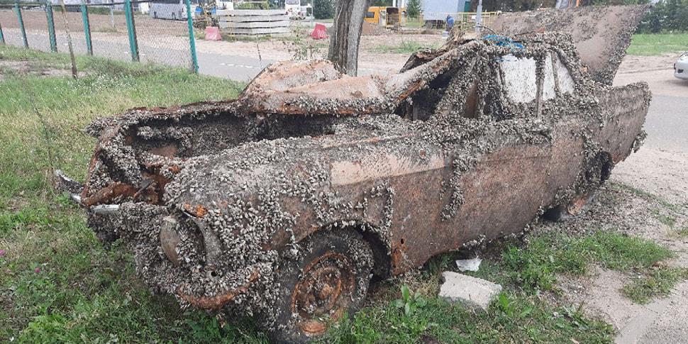 Старый автомобиль, покрытый ракушками, замечен на обочине столичной улицы